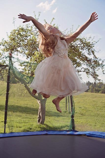 dívka v šatech na trampolíně