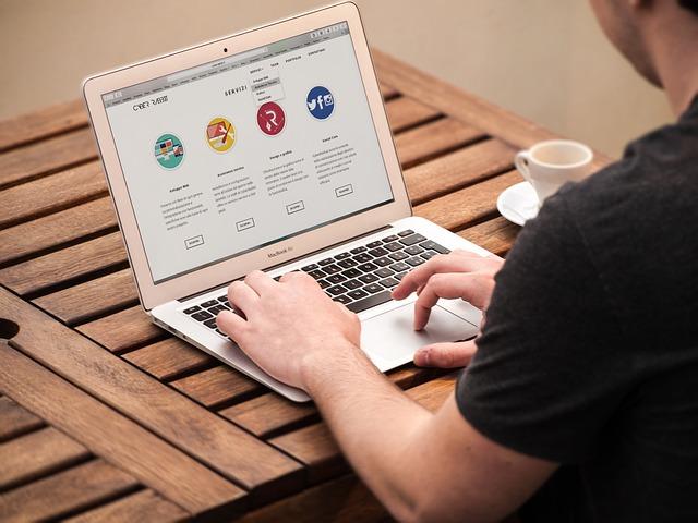 Notebook na stole s otevřenými stránkami a za ní ještě běžící monitor