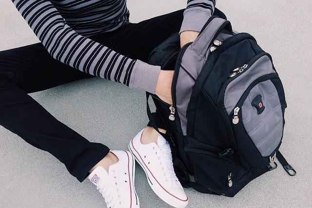 Dítě sedící na zemi a rukama rozevírající batoh