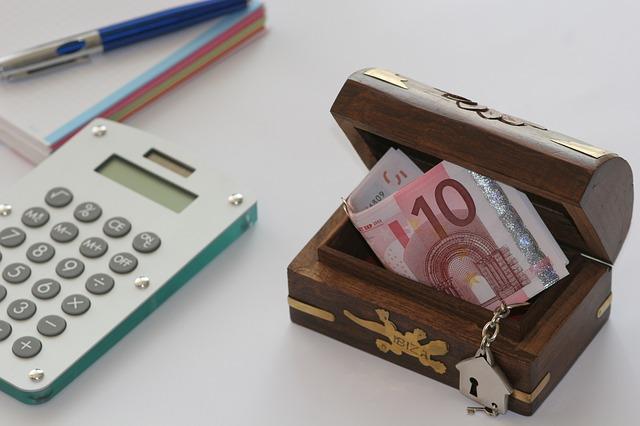 kalkulačka a malá truhlice s bankovkami