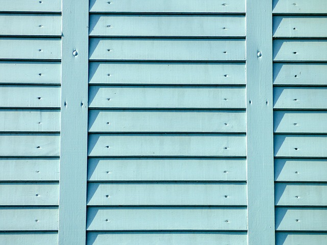 Detail bledě modře natřeného plotu