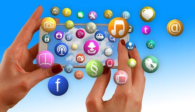 modré pozadí, ruce drží mobilní telefon na šířku.jpg