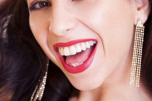 úsměv modelky s řetízkovými náušnicemi
